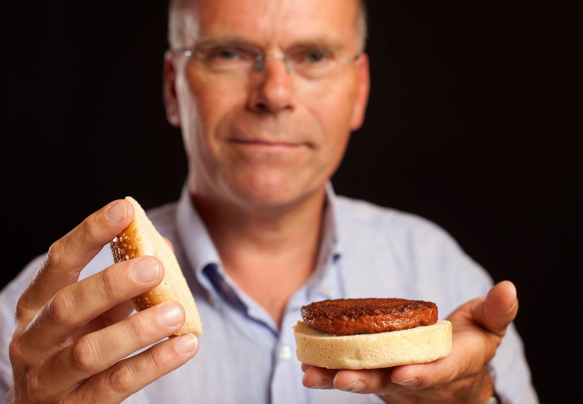Dr. Mark Post mit Clean Meat Burger in der Hand