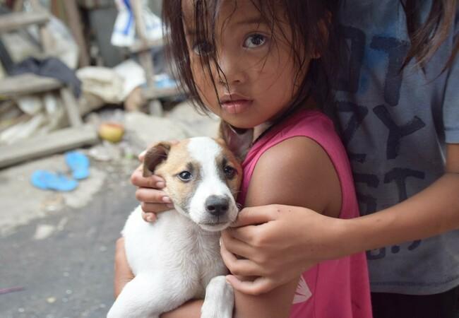 Meisje in Cambodja houdt een puppy in haar armen