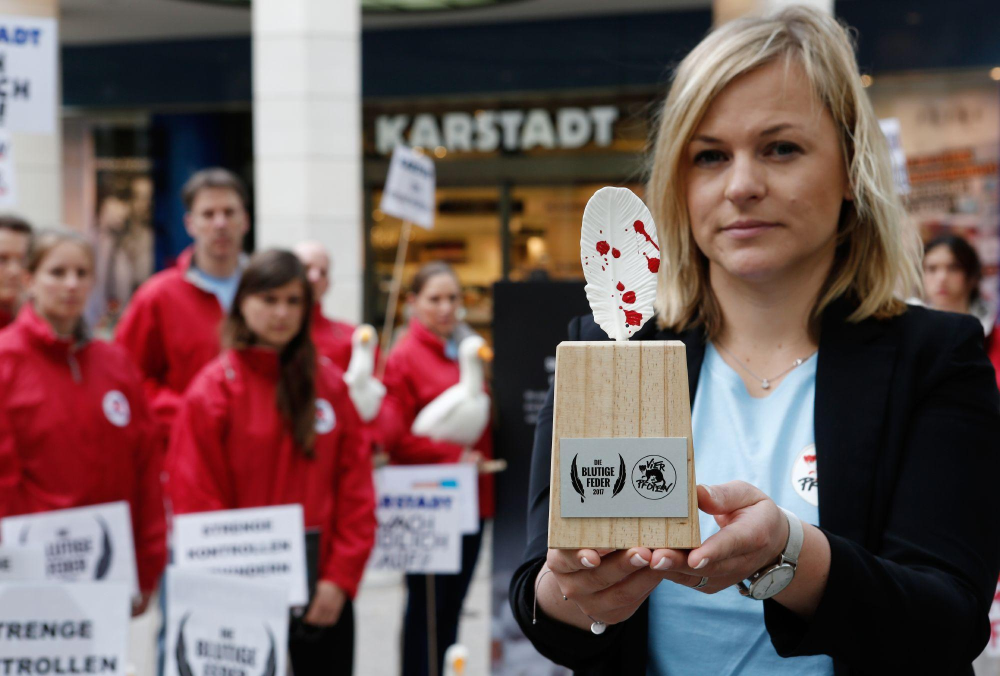 Head of Programs for FOUR PAWS Germany Denise Schmidt hands Bloody Feather award to fashion company Karstadt
