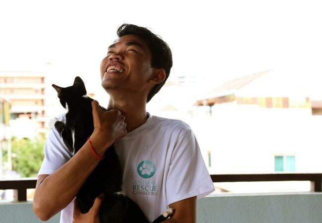 Coördinator Kimson Sann knuffelt in Animal Rescue Cambodja T-shirt met geredde zwerfkat