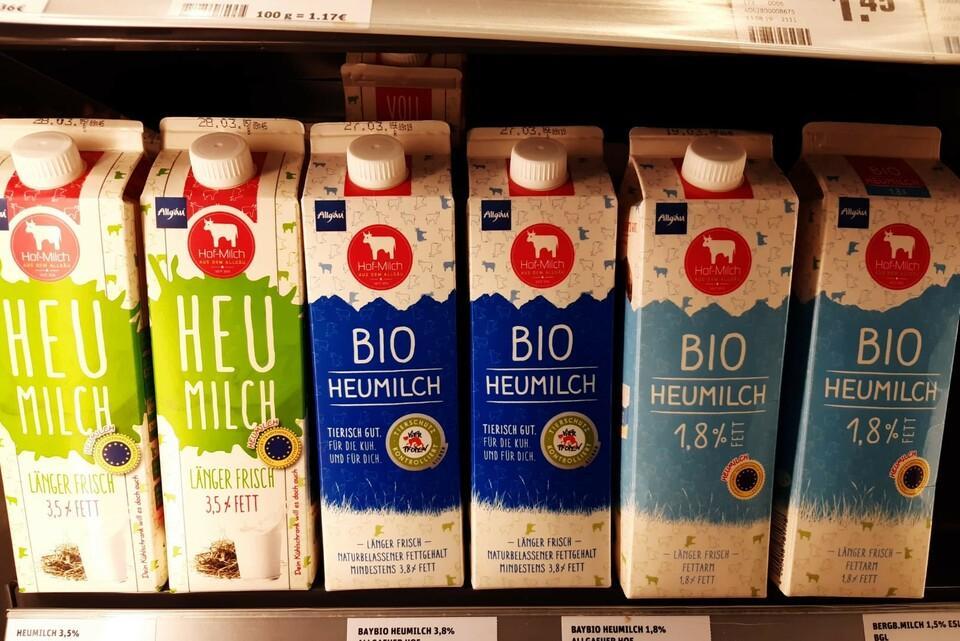 """Milchverpackungen mit dem """"Tierschutz kontrolliert"""" Gütesiegel im Kühlregal eines Supermarkts"""