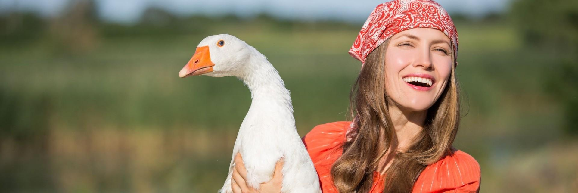 Happy woman holding a goose