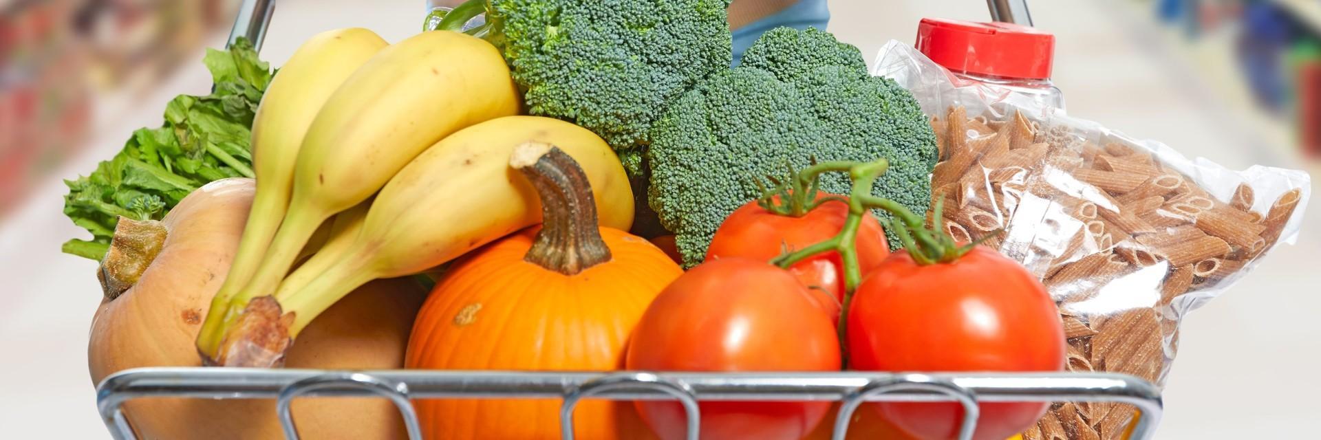Einkaufswagen mit Obst, Gemüse und Nudeln