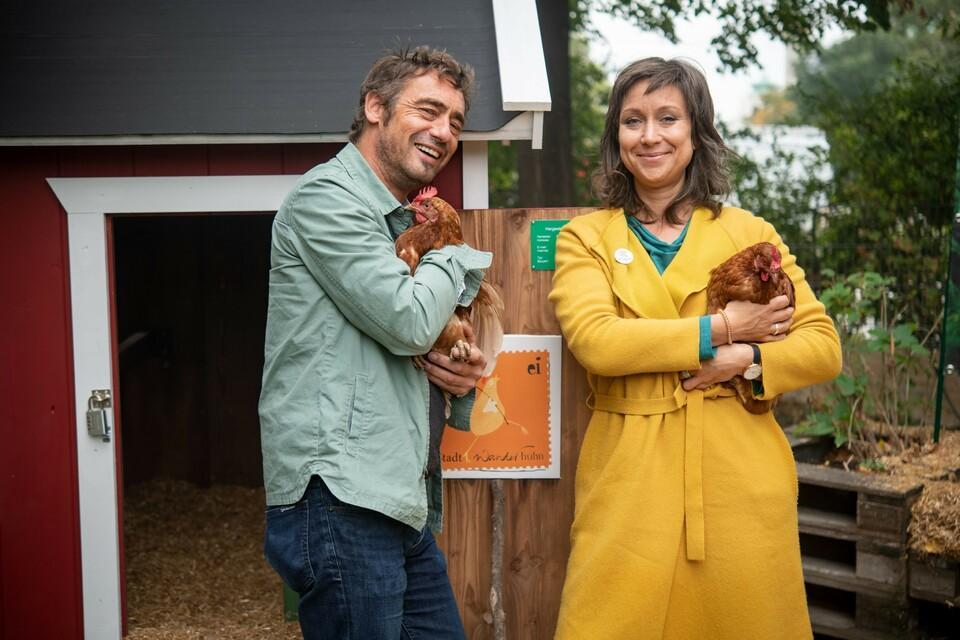 Landwirt und Mitarbeiterin von VIER PFOTEN kümmern sich um Hennen