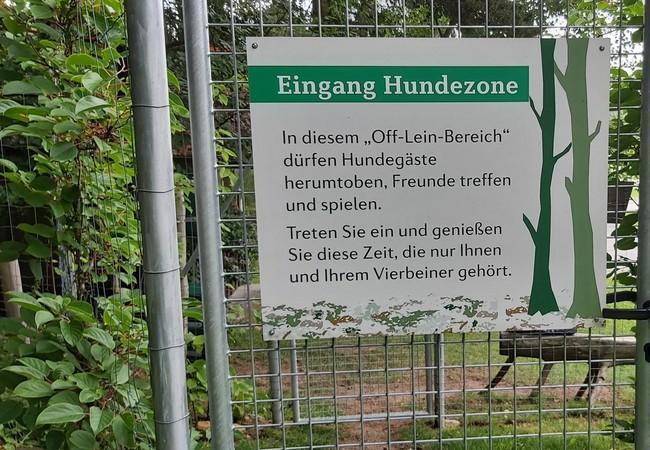Schild über Beschreibung der Hundezone beim Eingang in dieselbe