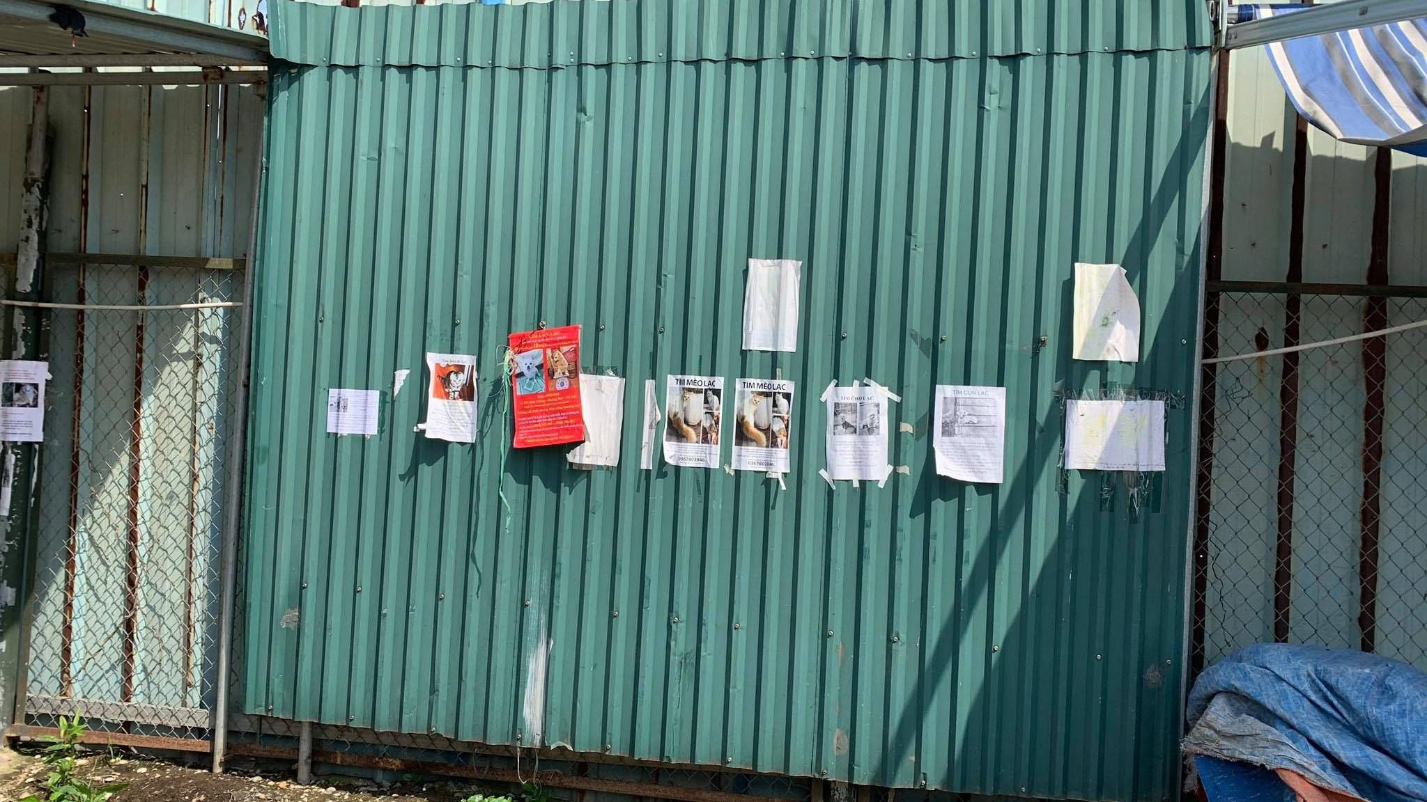 Posters of missing cats outside a dog and cat meat market in Vietnam