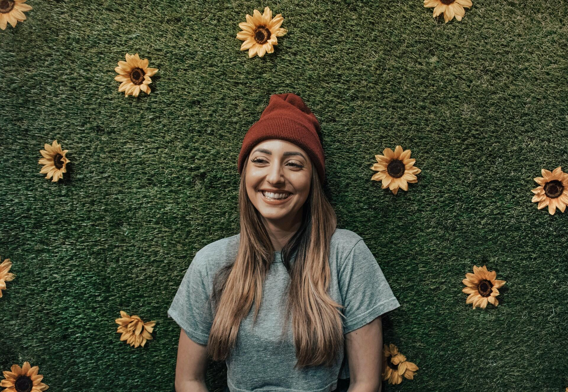 A happy woman looking at the camera surrounded by sunflowers