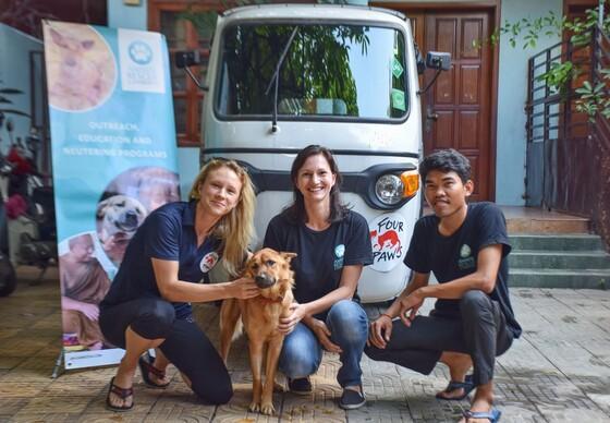 Teamleden VIER VOETERS en Animal Rescue Cambodja poseren voor tuktuk met hond