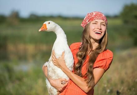 Beautiful woman holds a goose