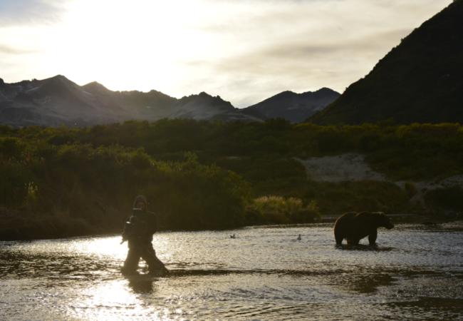 Roman Droux steht im Fluss mit der Kamera