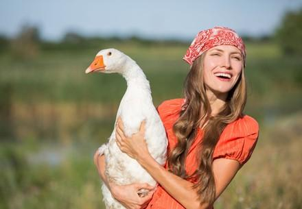 A happy woman with a goose
